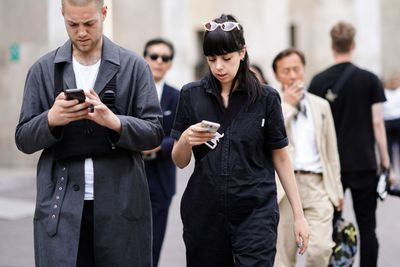 People walking down the street texting