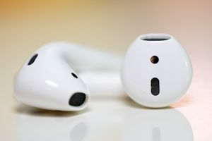 Two Apple AirPods in front of a yellow and orange background.