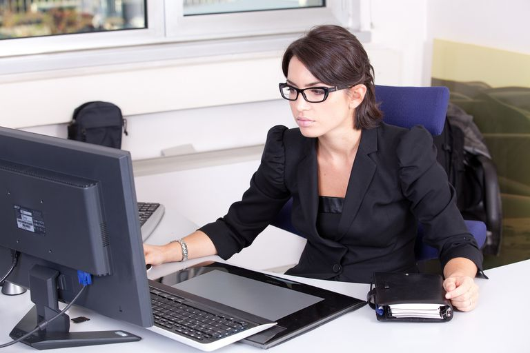 Woman working on computer with notebook