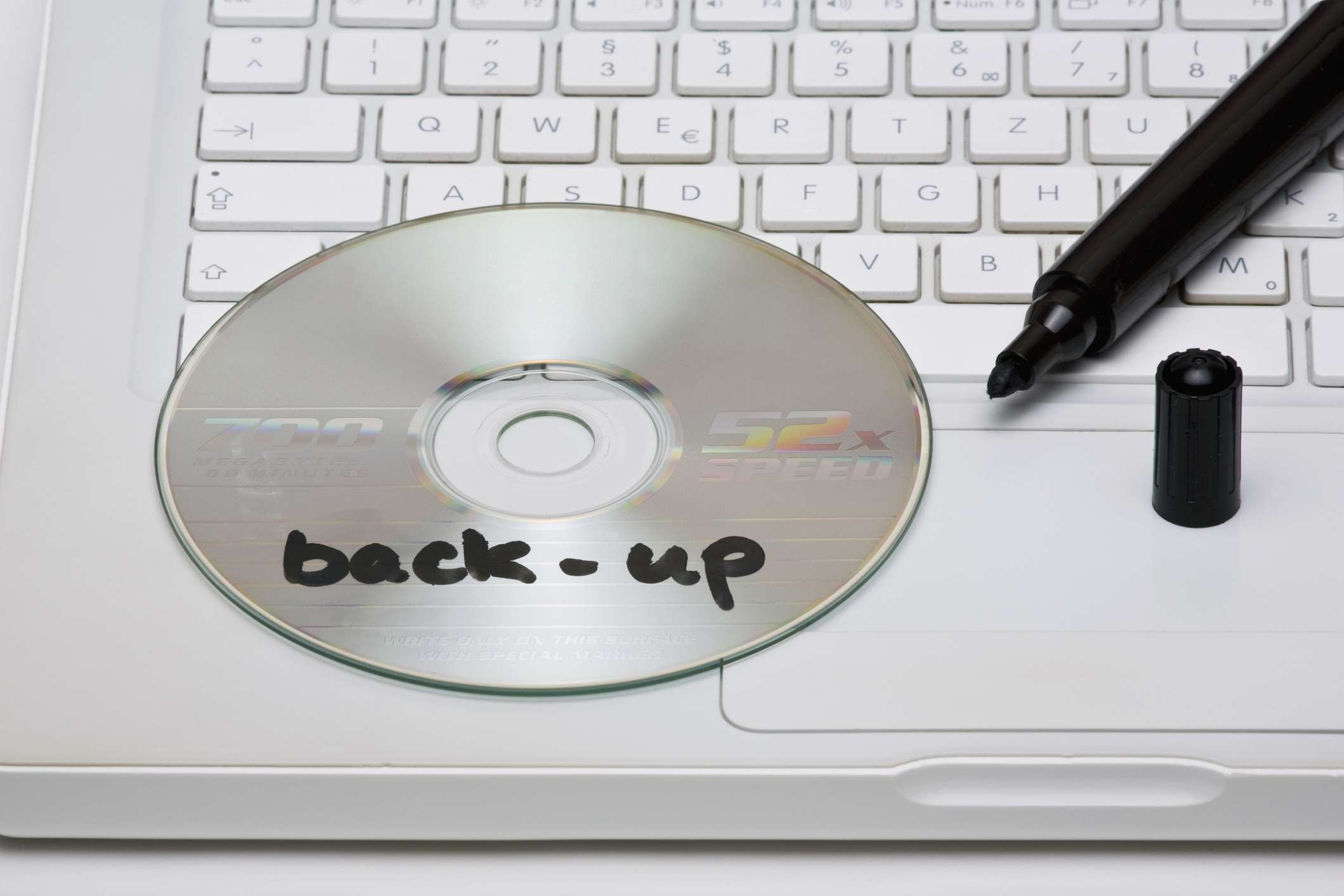 Detail of a back-up DVD disc and a marker on a laptop