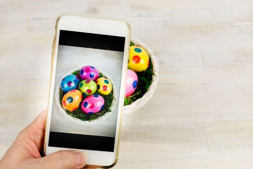 A person using a smartphone to take a picture of a bowl containing decorated Easter eggs