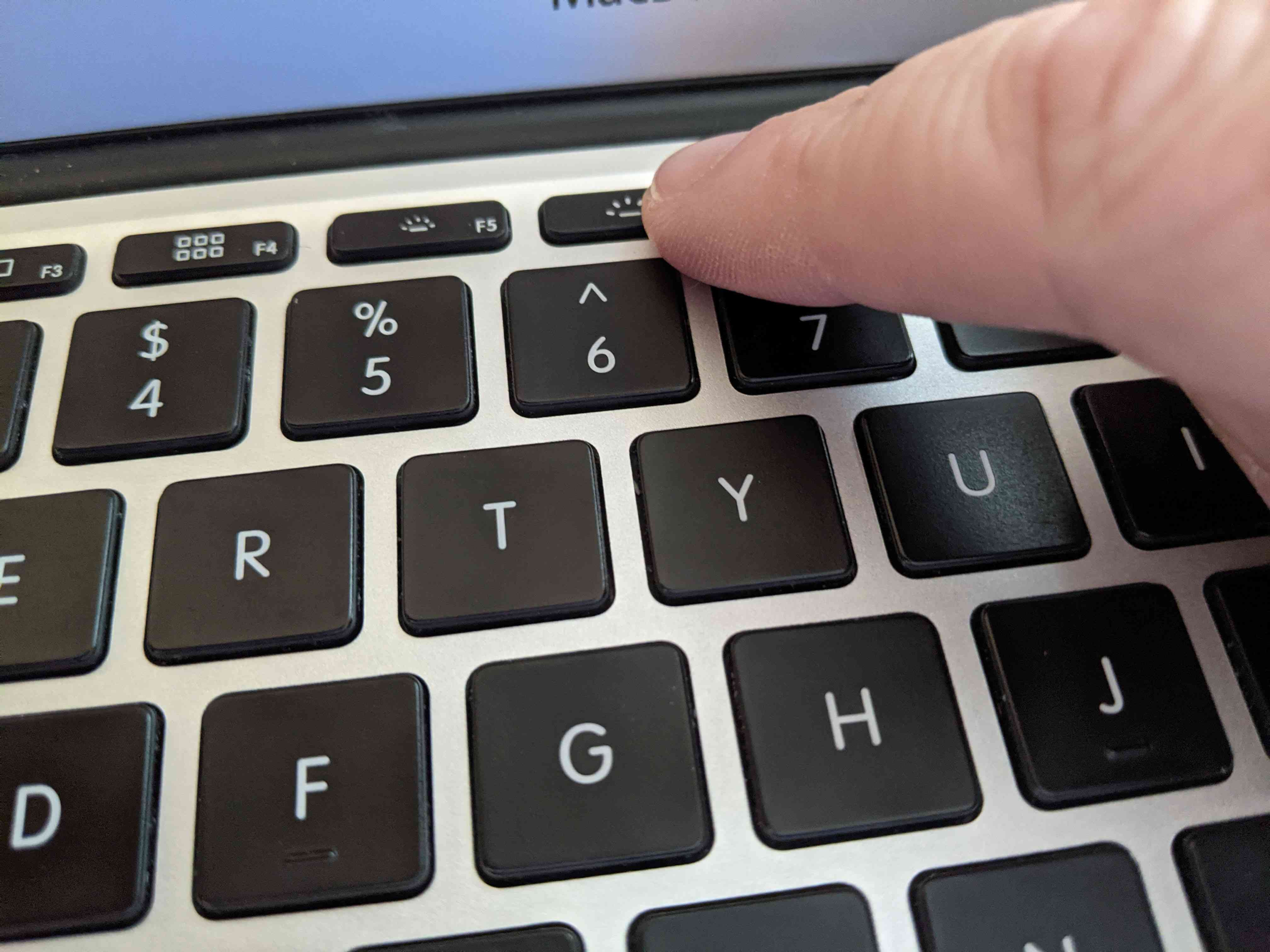 Pressing the Increase Button on a MacBook.
