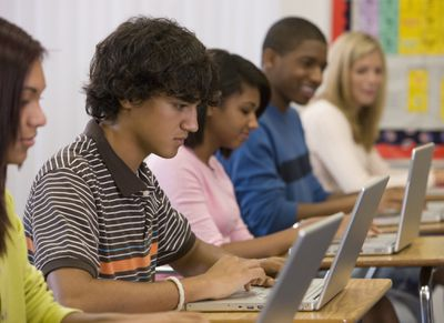 A group of teenagers sitting down side by side looking at their laptops