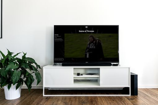 A TV on an entertainment center showing Games of Thrones.