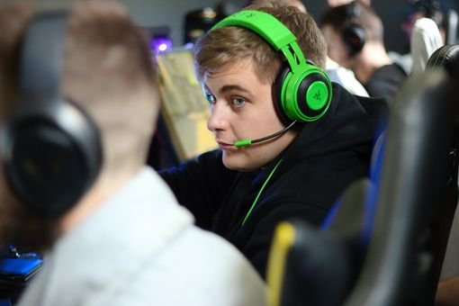Man sitting at gaming computer, wearing a lime green and black gaming headset.