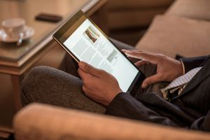 Cropped shot of young businessman sitting on hotel sofa reading digital tablet