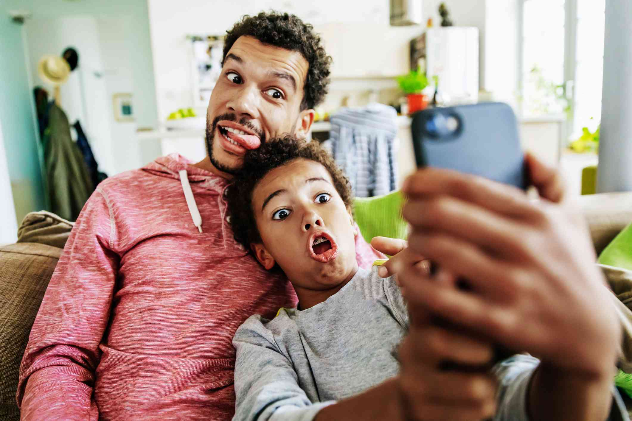 A father and son making funny faces while taking a selfie