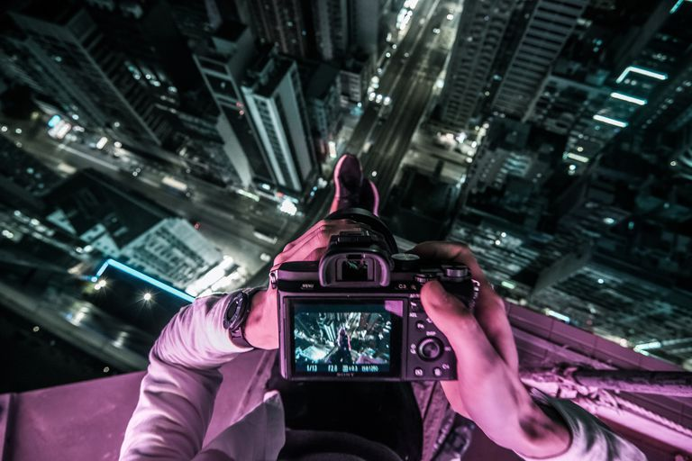 Midsection Of Man Photographing Illuminated Cityscape At Night