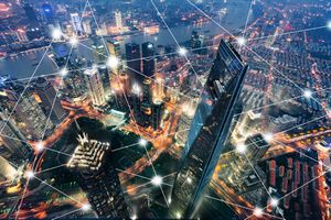 Cityscape superimposed with network nodes represented by bright lights and lines