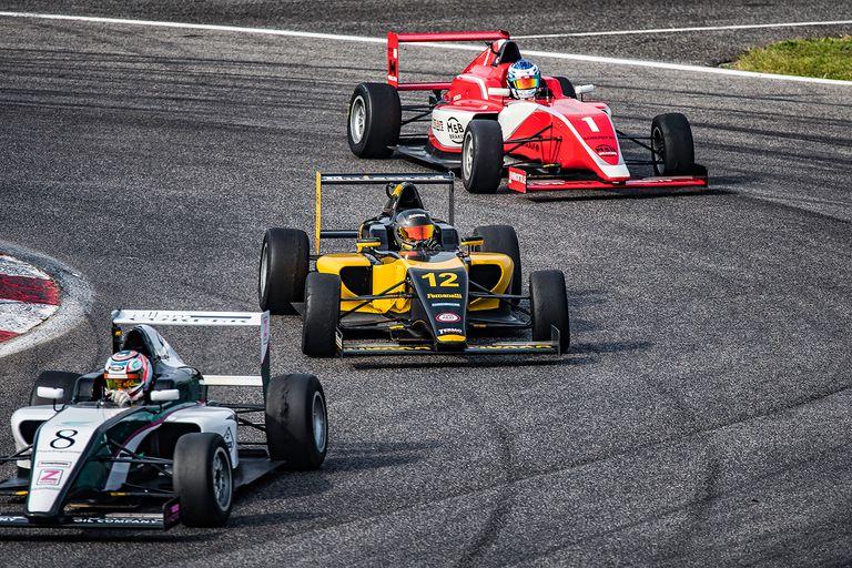 Men driving formula racing cars