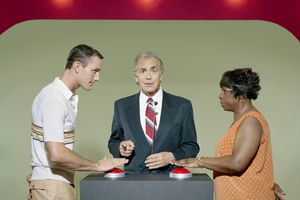 Two contestants and host in a mock game show.