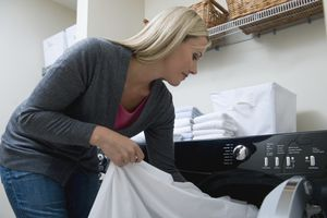 Woman unloading laundry from a dryer