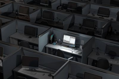 Office cubicles at night with one computer still on