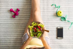 Overhead view of someone sitting with a bowl of salad and an smartphone.