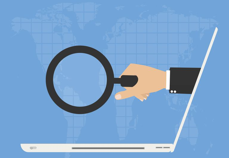 Hand holding magnifying glass extending out of computer screen illustration