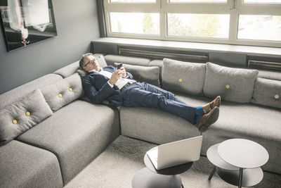 Man on couch with smart phone using laptop wifi