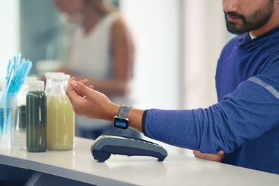 Man paying at register with a Fitbit Versa smartwatch using Fitbit Pay