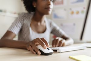 A close-up of a woman as she uses a mouse and wireless keyboard at a desk