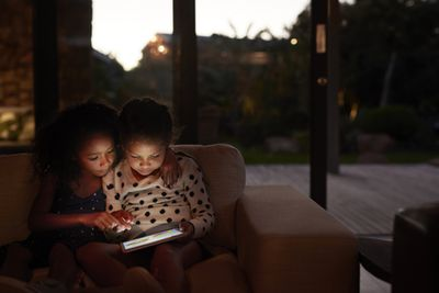 A woman and her child are sitting on a couch in the dark looking at a portable gaming device