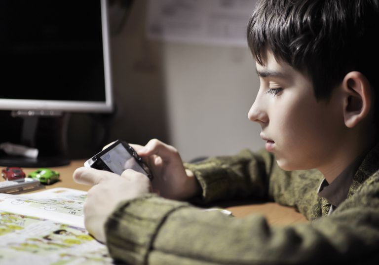 Child using a PSP at their desk