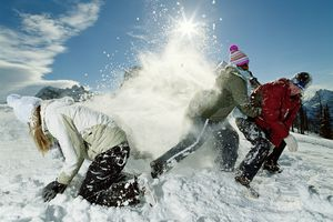 Three people playing in snow while the sun is shining