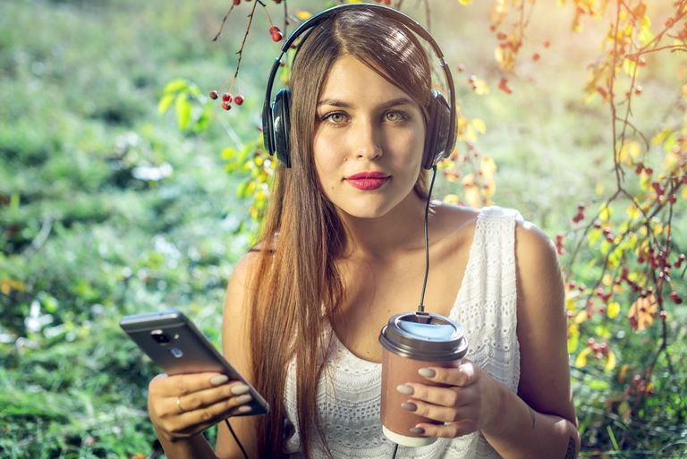 Woman wearing over-ear headphones connected to an Android phone while holding a coffee