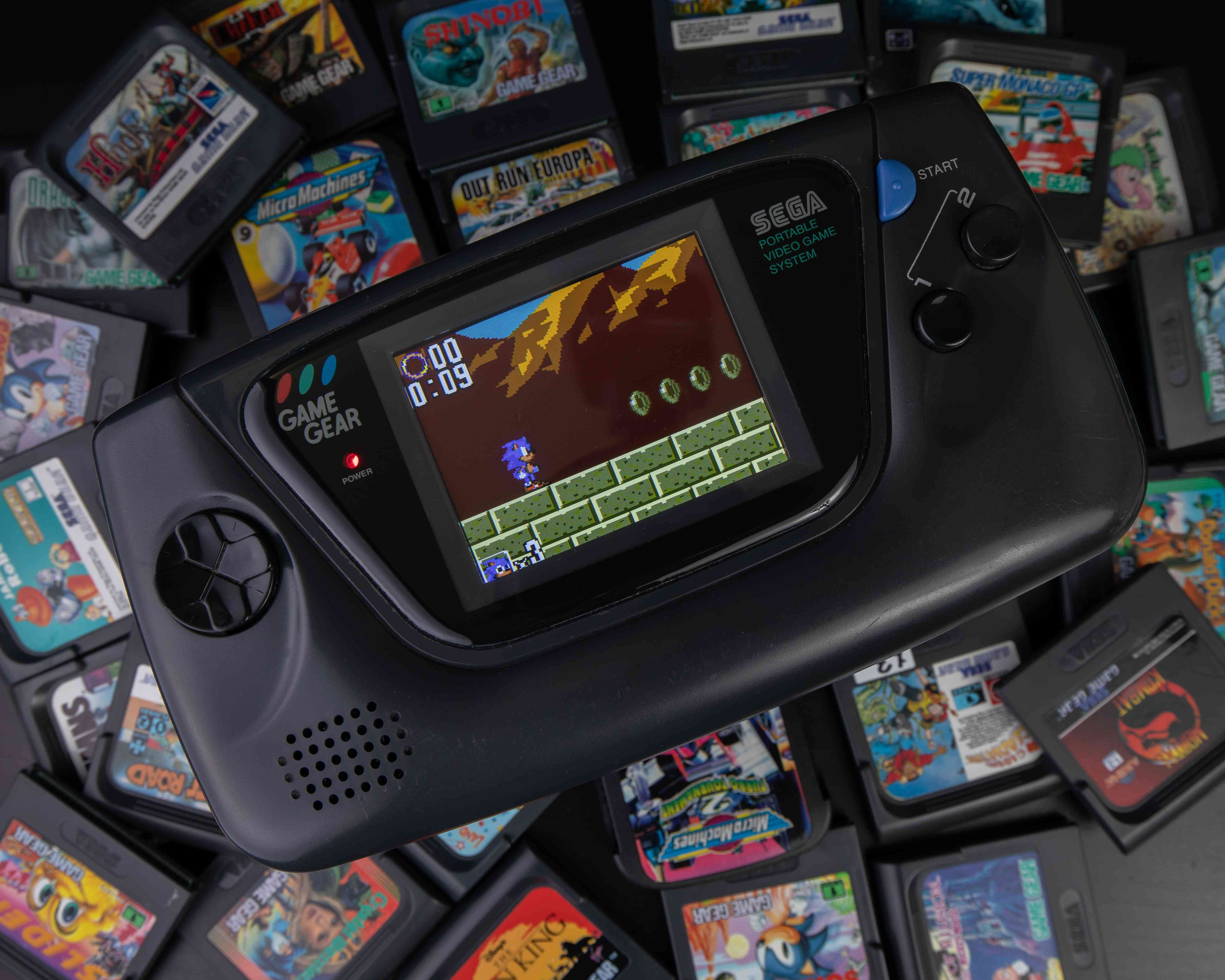 A Sega console surrounded by gaming cartridges.