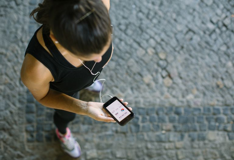 An image of a woman using an app on her smartphone while working out.