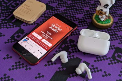 An iPhone with AirPods Pro playing Spatial Audio in Apple Music.