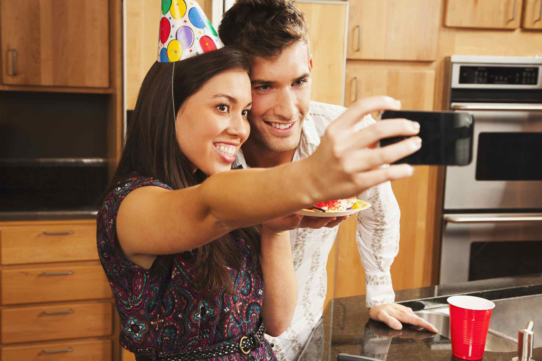 An image of a man and a woman posing for a selfie at a birthday party.
