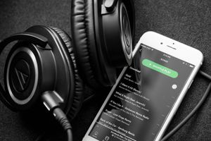 Spotify displayed on a phone with headphones nearby.