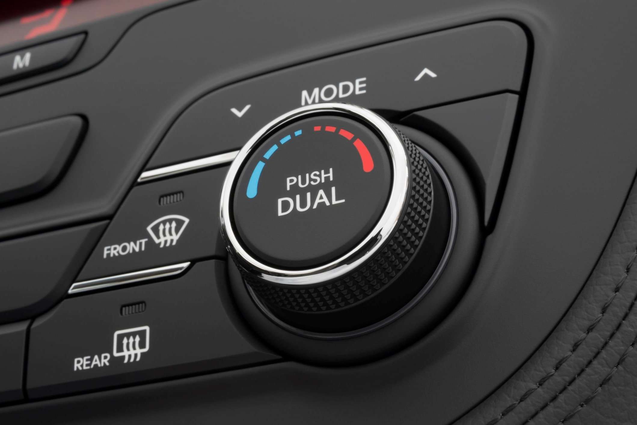 Temperature control dial and defroster buttons inside a car