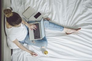 A woman sitting on a bed browsing a laptop with a smartphone and notebook next to her