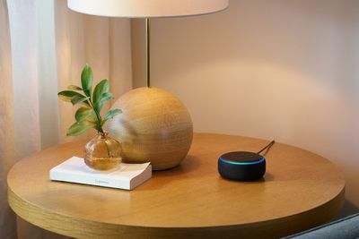 An Amazon Echo Dot on a wooden table
