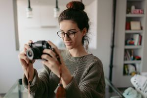 Young photographer using camera in apartment
