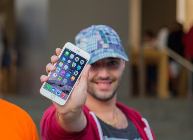 A smiling man proudly shows his iPhone