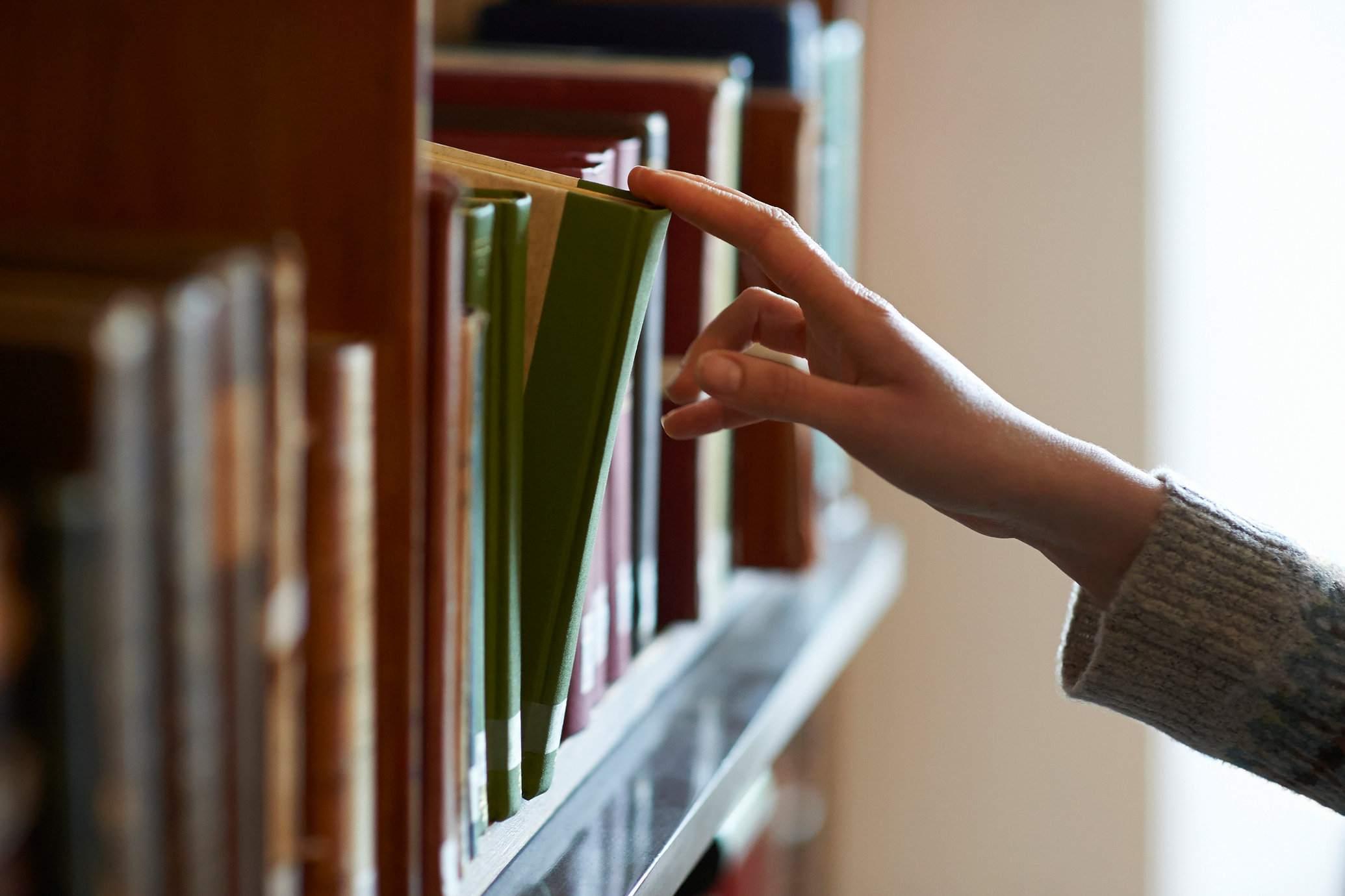 A hand picking a book on a book shelf