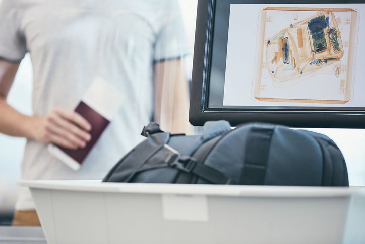 Traveler holding passport and waiting for x-ray control luggage.