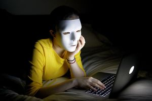 Anonymous woman in mask on internet at night