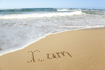 'I am' written in the sand on a beach