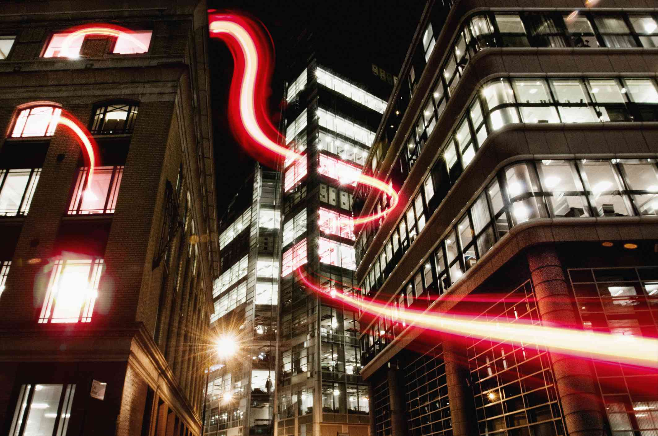 A concept image with a dynamic fibre optic light trail running through and around buildings in a city.