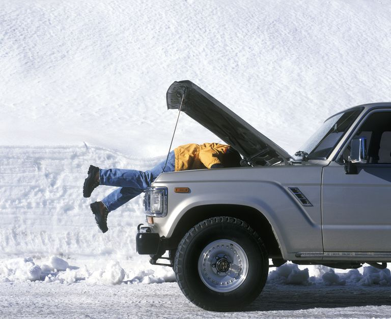Man removing a car battery in the dead of winter
