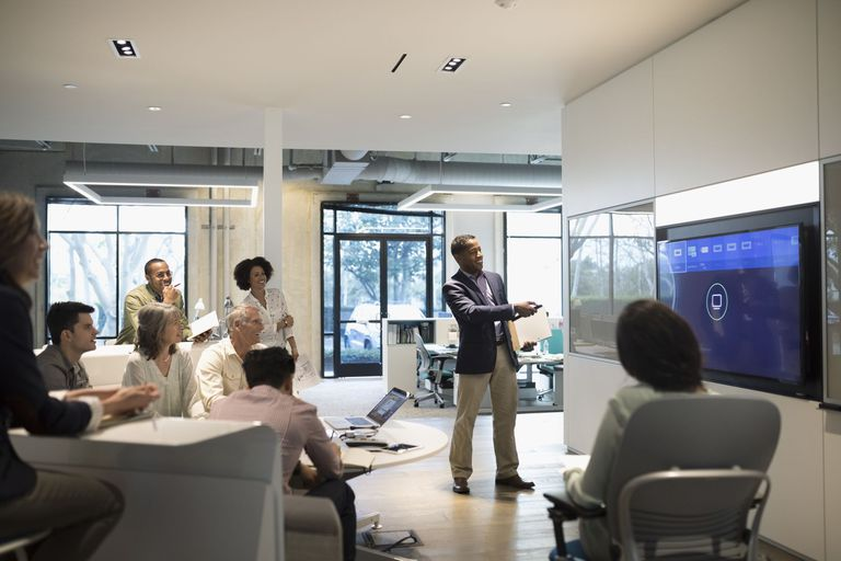 Businessman leading audio visual presentation in conference room meeting
