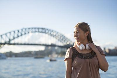 Woman in front of bridge with wireless headphones