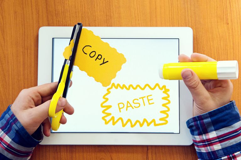 Scissors cutting paper that says copy, tablet says paste