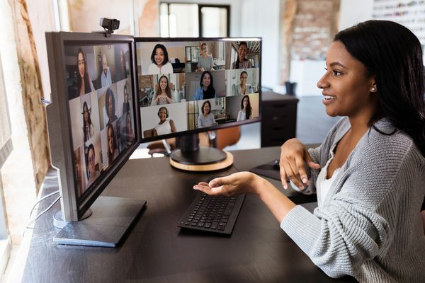 Someone speaking at a virtual meeting in a home office with two computer screens.