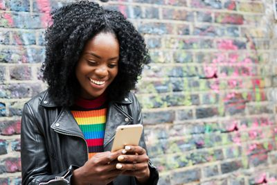 Woman standing in front of a brick wall, smiling at her smartphone