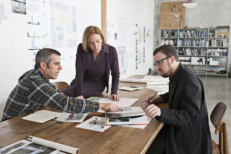Three people consulting over graphic design project