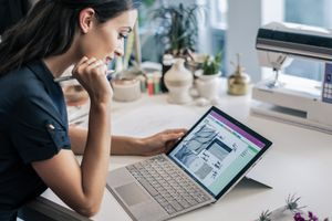 Business woman holding a Surface Pen and working with a Surface Pro