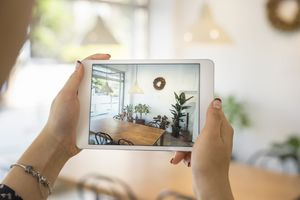 Woman holding an iPad, viewing her dining room through its camera lens